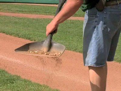 Photo: A groundskeeper uses a shovel to sift through topdressing.